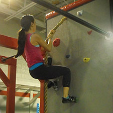 Woman climbing rock wall with rope