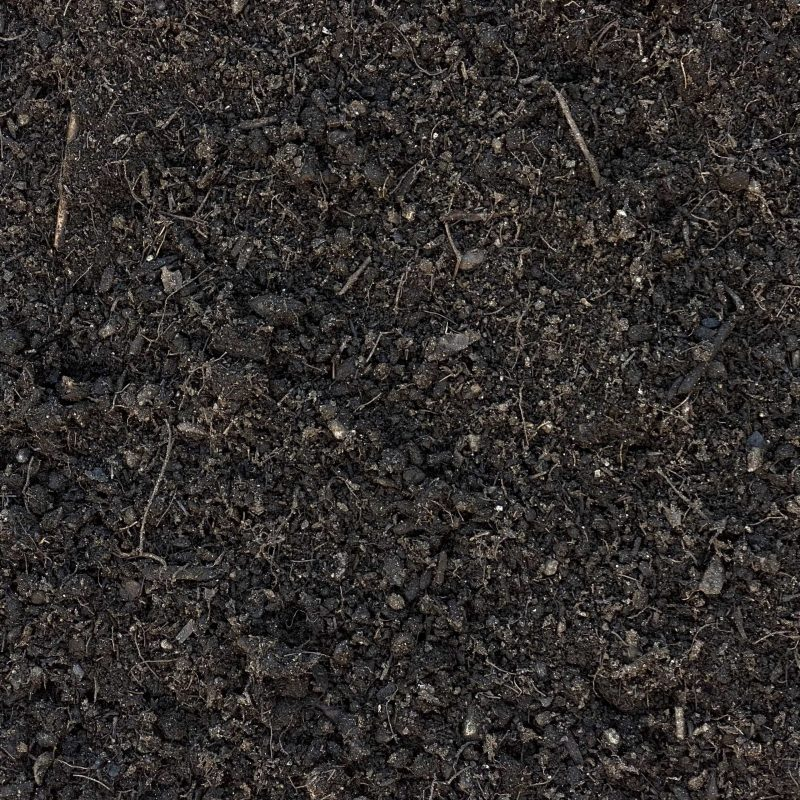 This image displays our organic compost. It is a dark brown color and filled with organic material from trees and plants.