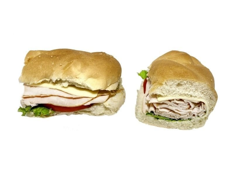 Pictured is a turkey and cheese sandwich with lettuce on a braided roll!