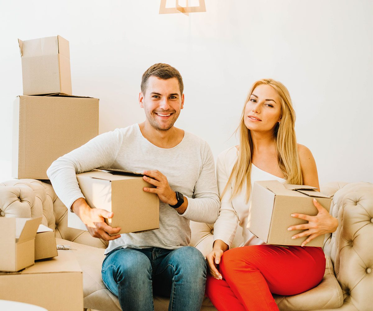 Man and woman sitting on couch holding moving boxes