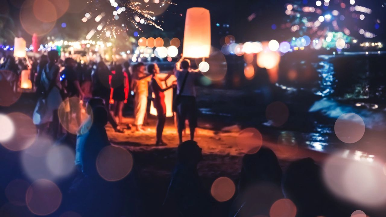 Party of people releasing lanterns into the air at night