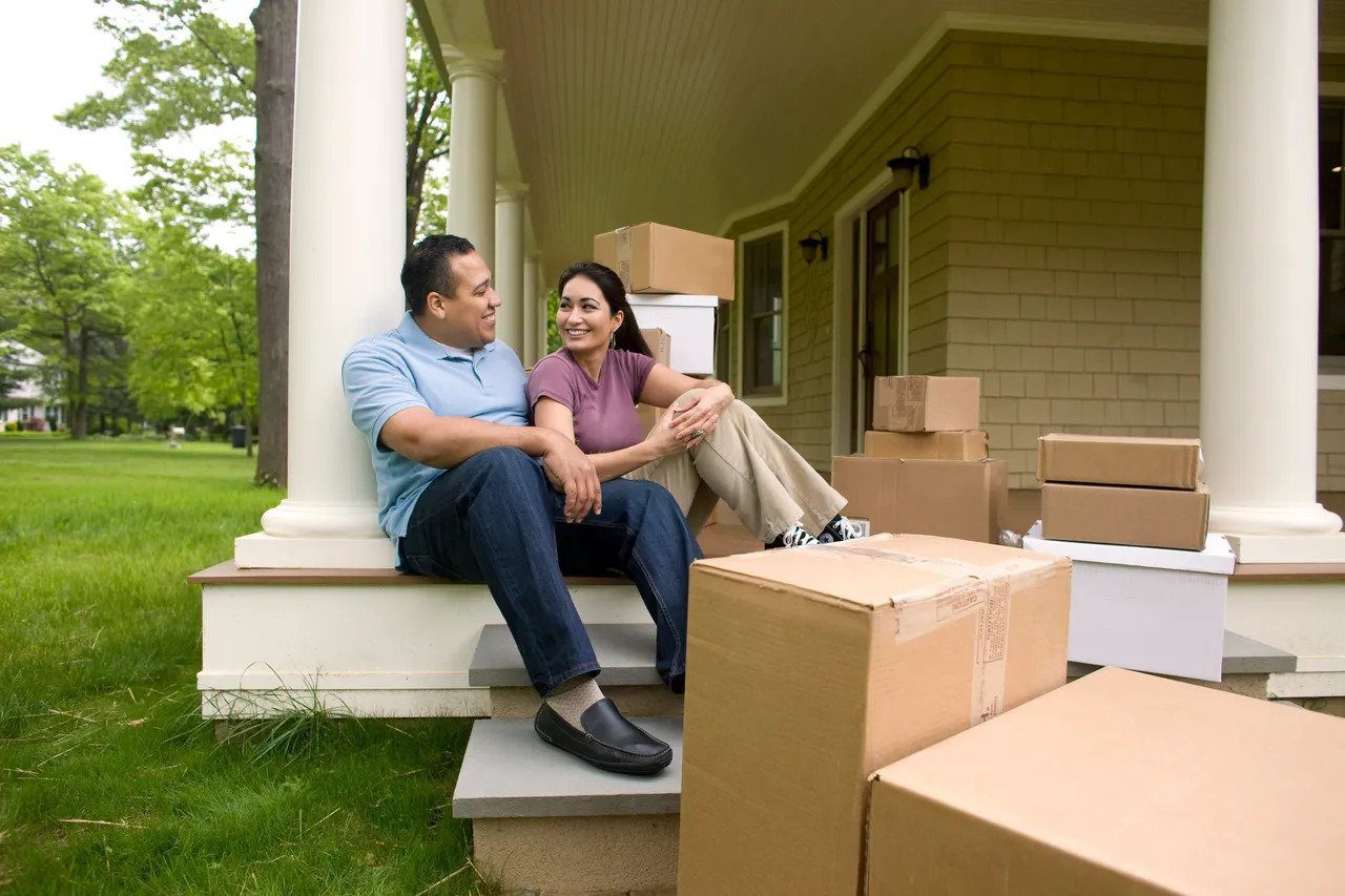 Couple sitting on front deck with moving boxes smiling