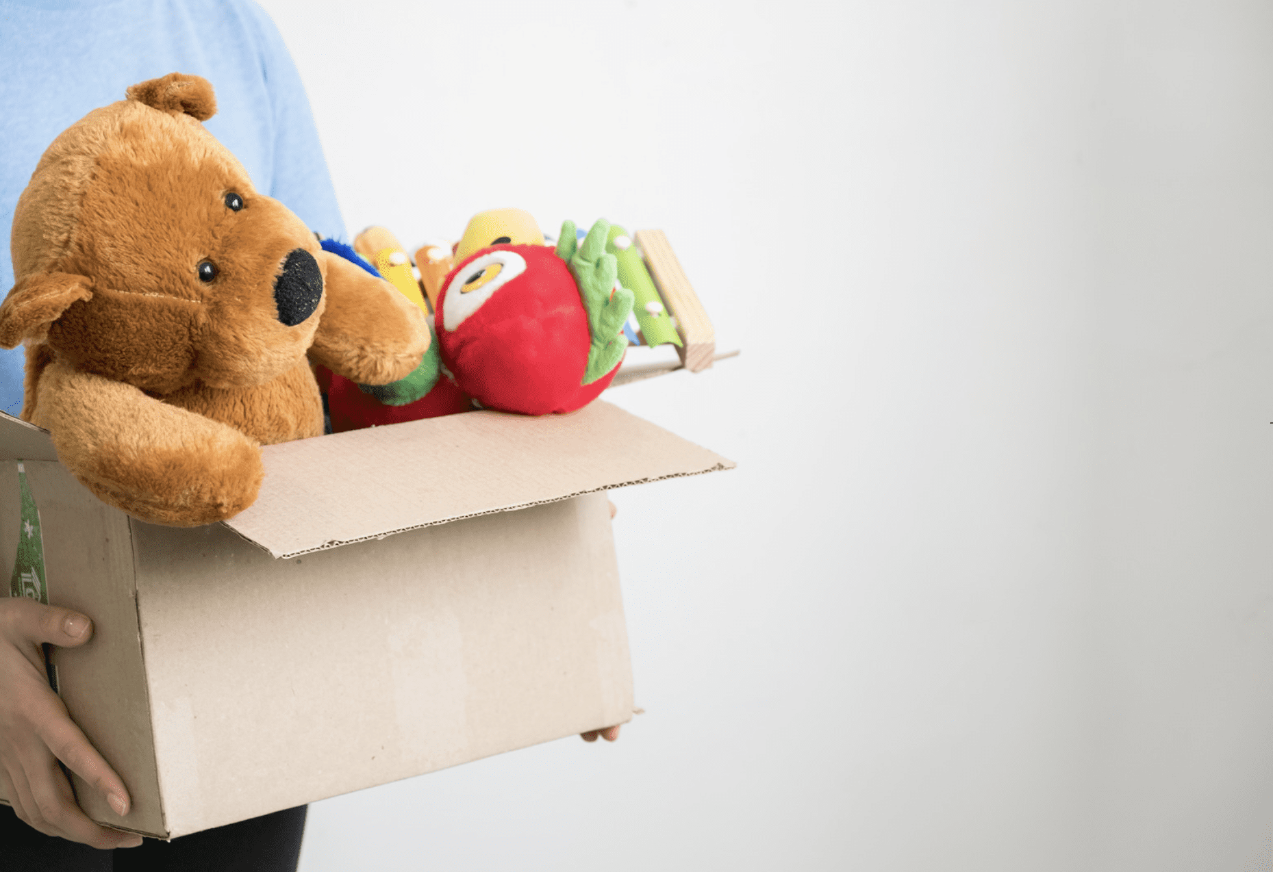 Person holding a box of stuffed animals to donate