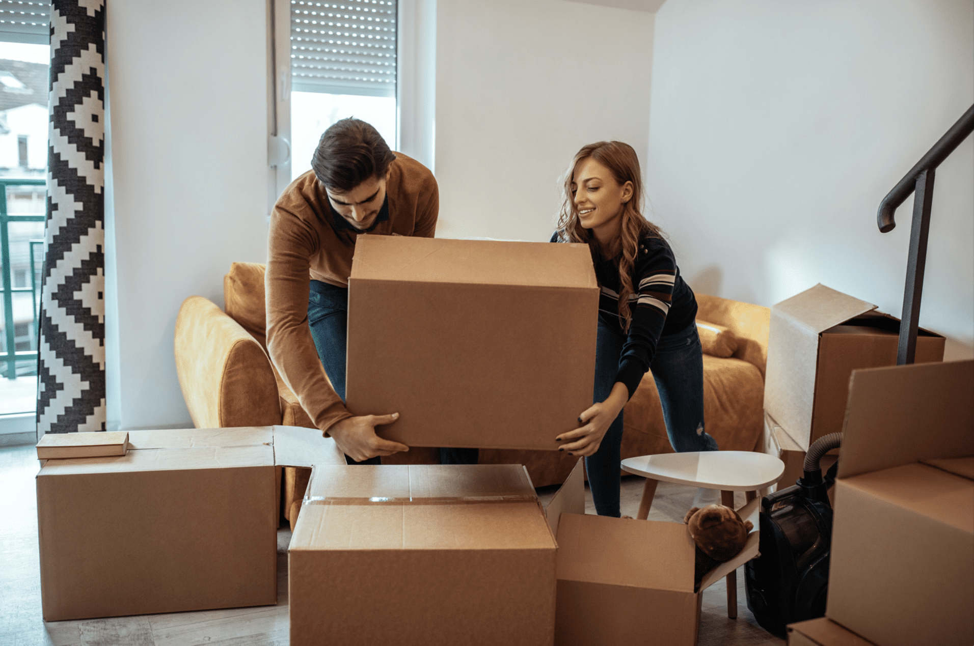 Couple lifting and stacking boxes to move