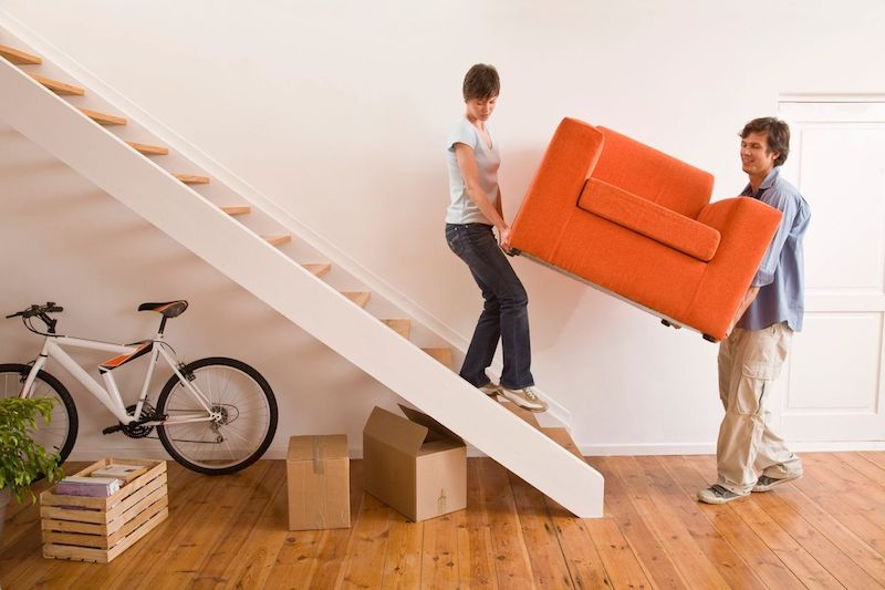 Woman and man carrying chair down the stairs to move