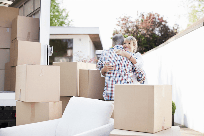 Couple hugging by a moving truck with boxes