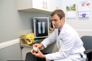 Dr. Fehm in an exam room showing an x-ray and bone models