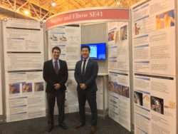 Dr. Peter S. Vezeridis standing by his presenatation at the AAOS