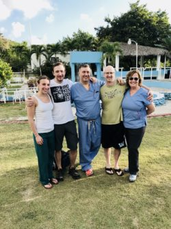 Outdoor photo of Dr. Levine, Dr. Kozanek, Bill Martin, Beth Keelan and Lauren Doherty in the Domincan Republic on a medical mission trip