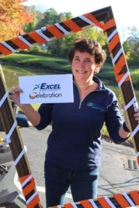 Dr. Feiler standing and holding a frame with a sign that says Excel Celebration